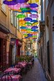 Historisk gränd och restaurang i Béziers i Frankrike i skuggan av paraplyer Arkivfoto