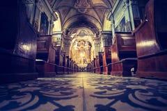Historisk katolsk kyrka: Träkyrkbänkar i rad och altarebreddkors royaltyfria foton