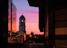 Historisk kyrklig klocka som reflekterar vibrerande färger på solnedgången royaltyfri fotografi