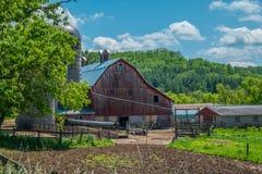 Historisk lantlig gammal röd ladugård arkivbild