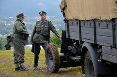 Historisk lastbil med två iklädda tyska nazilikformig för män under historisk reenactment av striden för världskrig 2 Royaltyfri Bild
