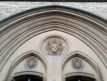 Historisk onramental garnering ovanför en kyrklig dörr Arkivfoto