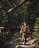 Historisk reenactment av den ryska inbördeskriget i Uralsna i 1918 Soldaten av den vita armén går på en skogväg Arkivbilder