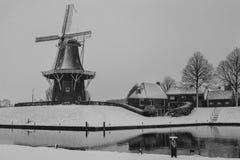 Historisk väderkvarn i snö bredvid vatten Fotografering för Bildbyråer