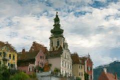 Historiska österrikiska byggnader reflekterade i vattnet royaltyfri bild