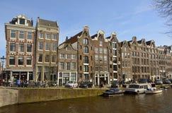 Historiska bostads- byggnader med reklamfilmen shoppar på bottenvåningen på hörnet av den Prinsengracht kanalen och den Reestraat Arkivbilder