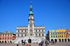 Historiska byggnader i marknadsfyrkant i Zamosc, Polen Arkivfoto
