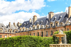 Historiska byggnader på ställedesen Vosges i Paris Arkivfoton