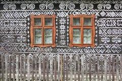 Historiska fönster på ett hus i den byÄŒiÄ en många Arkivbild