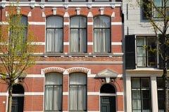Historiska fasader med carvings som lokaliseras längs den Oude delftfajanskanalen, delftfajans royaltyfri fotografi