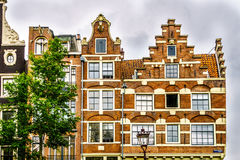 Historiska hus med moment och Klocka gavlar i Amsterdam arkivfoto