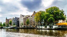 Historiska hus med olika typer av gavlar från medeltiden längs kanalerna i Amsterdam royaltyfri bild