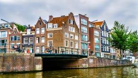 Historiska hus med olika typer av gavlar längs kanalerna i Amsterdam arkivfoto