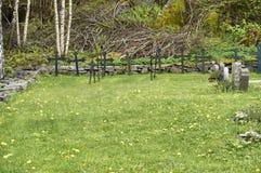Historiska kors och gravstenar i en liten kyrkogård arkivbilder