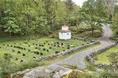 Historiska kors och gravstenar i en liten kyrkogård arkivbild