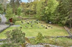 Historiska kors och gravstenar i en liten kyrkogård royaltyfri foto