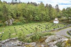 Historiska kors och gravstenar i en liten kyrkogård arkivfoto