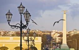 Historiska lyktor och en obelisk med den guld- örnen Arkivbild
