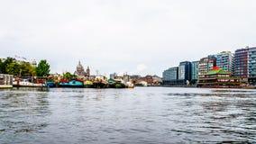 Historiska och moderna byggnader längs den upptagna hamnen av staden av Amsterdam Royaltyfri Fotografi