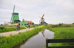 Historiska väderkvarnar & turister som cyklar i Zaanse Schans, Nederländerna Royaltyfri Fotografi