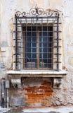 Historiskt fönster med marmorgarneringar och smidesjärnbråckbandet Arkivfoton
