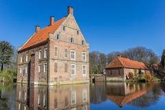 Historiskt hus Welbergen med reflexion i vattnet i Ochtrup arkivfoto