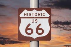 Historiskt huvudvägtecken för USA Route 66 med solnedgånghimmel arkivbild