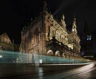 Historiskt stadshus i Bremen, Tyskland på natten med domkyrkan för St Paul ` s och kyrkan av vår dam i bakgrunden och spårvagnpas arkivfoto