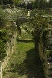 Historiskt stena passagen med bågen på den roman amfiteatern i Siracusa i Sicilien royaltyfria bilder