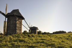 History. Ancient windmill as in old fairytale in the green meadow Royalty Free Stock Photography