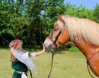 History lovers - small girl in a historical costume holding a Hafflinger horse Royalty Free Stock Photography