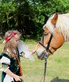 History lovers - small girl in a historical costume with a Hafflinger horse Stock Image