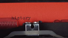 History - typed on a old vintage typewriter. Printed on red paper. The red paper is inserted into the typewriter stock footage