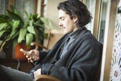 Hiszpański młody człowiek używa smartphone obsiadanie na tarasie obrazy stock