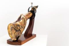 Hiszpańskiej garmażerii suchy leczący mięsny baleron, cała noga, jamon iberico bellota na jamonero stojaka selekcyjnej ostrości - obraz royalty free