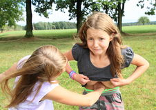 Hit in belly. Young brunette girl - kid hit by another blond girl with fist into stomach on meadow Stock Images