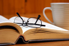 Hit the Books. A macro shot of an open book with reading glasses and a cup of coffee Royalty Free Stock Photo