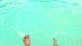 Hit the legs in the pool. Slow motion of Two legs hit the water to clear the pool with clear water stock footage