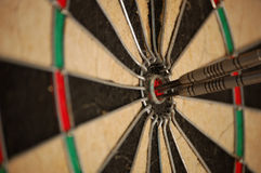 Hit the mark every time. Three darts inside the center of the bullseye, also called a hattrick. On target with every shot Stock Photos