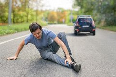 Hit and run concept. Injured man on road in front of a car.  royalty free stock photos
