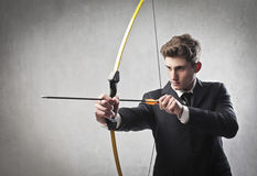 Hit the target. Young businessman drawing a bow Royalty Free Stock Photos