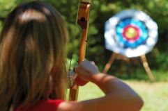 Hit the target. Female archer aiming at the target Royalty Free Stock Image