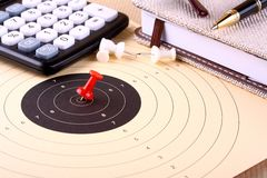 Hit the target - target, red pin, calculator, pen, notebook Stock Photo