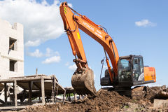 Hitachi orange Digger Moving Soil Photos stock