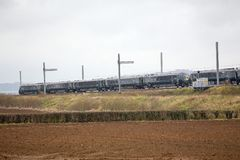 Hitachi Train passing partially completed electrification Royalty Free Stock Photo
