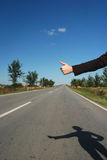 Hitch hike 05. Hitch hike on a road with shadow of hiker Stock Photo