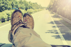 Hitch-hike travel. The cab of the truck. View of feet lying on the dashboard of the truck. Truck driving on a highway. The photo is purposely designed as a Royalty Free Stock Image