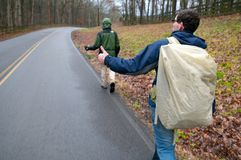 Hitch Hikers. Two men hitch hiking on an overcast rainy day Royalty Free Stock Photography