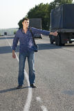 Hitch-hiking. Hitchhiking guy on the road Royalty Free Stock Images