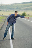 Hitch-hiking. Hitchhiking guy on the road Royalty Free Stock Image